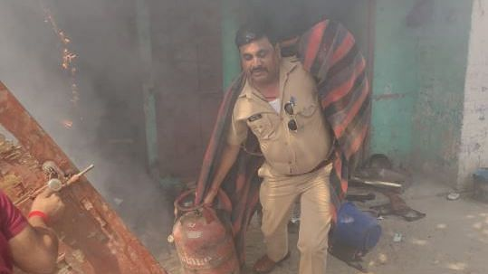 SI Akhilesh Kumar Dixit dragging LPG cylinders out from a house on fire.