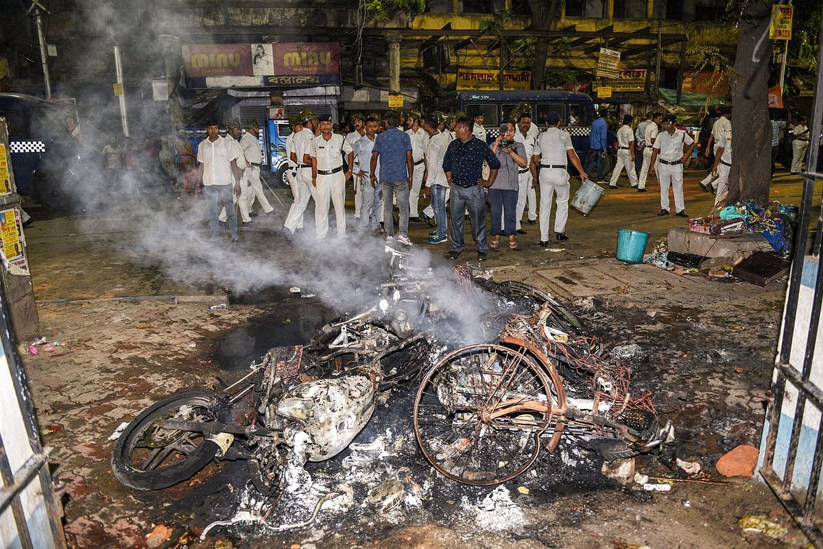 Police personnel look on near vehicles burnt by a mob during BJP President Amit Shah's election roadshow.