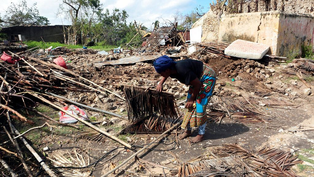A woman picks up pieces from her house which was damaged by Cyclone Kenneth in Mozambique on 1 May.