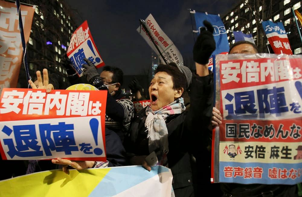 Anti-Abe protesters in Tokyo hold signs calling for Abe's resignation after his administration was ensnared in a corruption scandal, March 23, 2018.