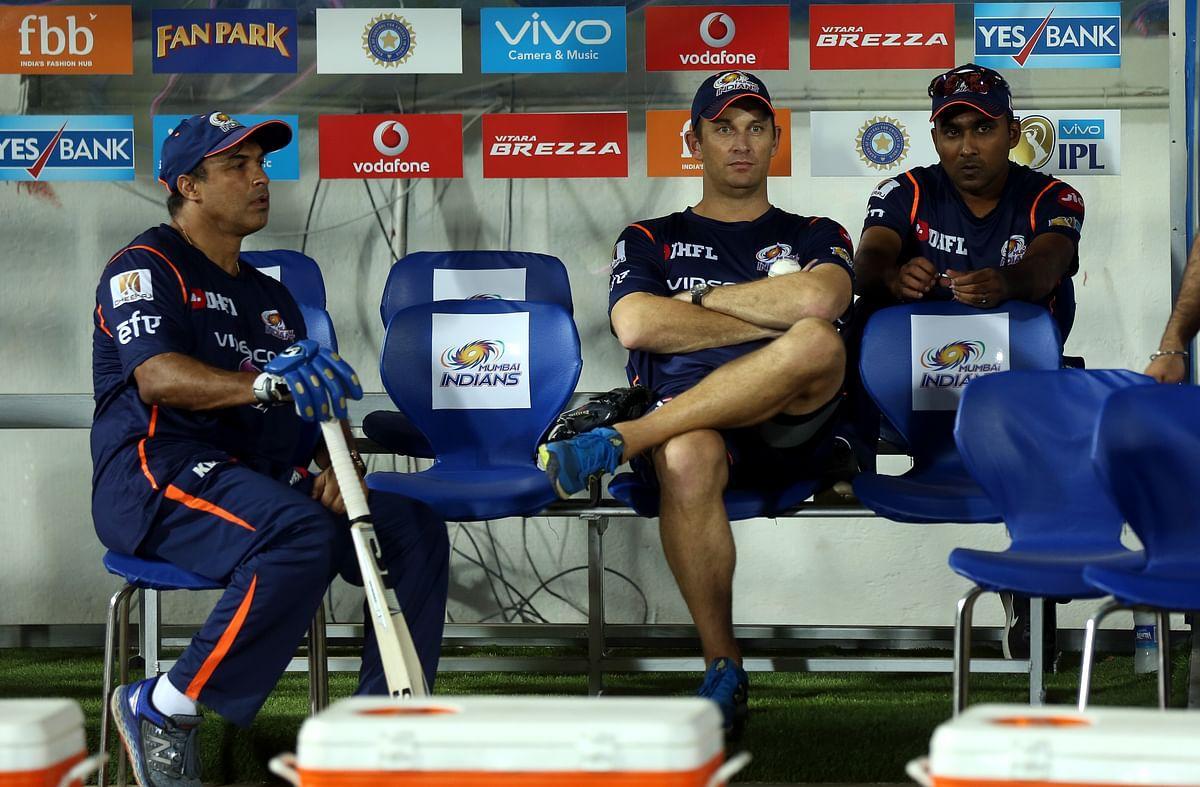 Mumbai Indians assistant and batting coach Robin Singh, bowling coach Shane Bond and head coach Mahela Jayawardene sit in the dugout during an IPL match.