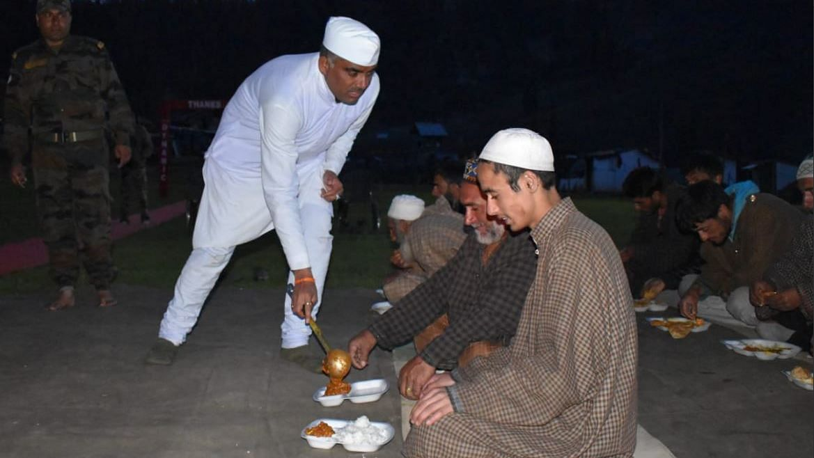 An army Panditji<i> </i>(priest) serves food to local civilians during Iftar at Dawar, Gurez in North Kashmir.