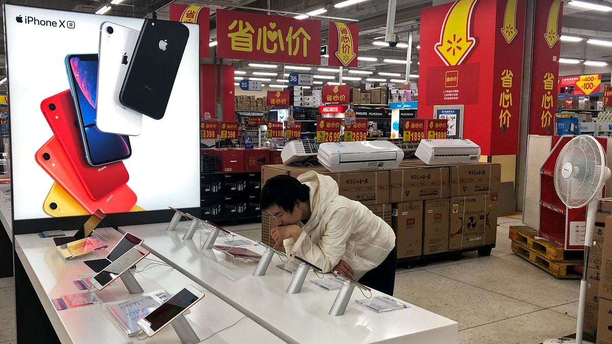 A man browses an iPhone unit on display at a section selling Apple's products together with Chinese made electric appliances at a hypermarket in Beijing.