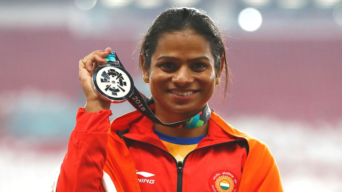 India's Dutee Chand celebrates on the podium after winning the silver medal in the women's 100m final during the athletics competition at the 18th Asian Games in Jakarta, Indonesia.