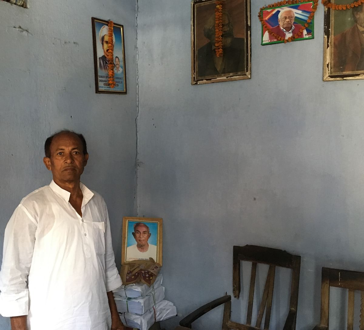 Comrade Ambika, with a picture of Ramashray Prasad Singh in background at CPI office in Jehanabad.