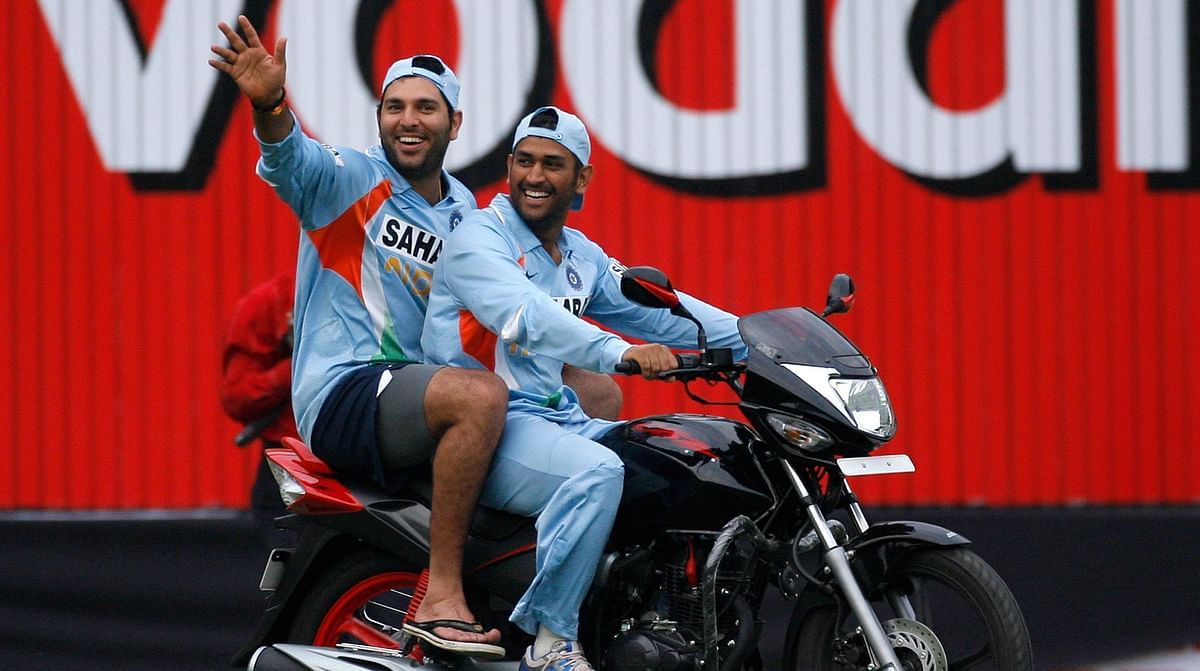 Yuvraj Singh (L) and India's captain Mahendra Singh Dhoni ride a bike which was given to Yuvraj Singh for winning the man-of-the-match award following India's win in the second ODI  against England in Indore, 17 November  2008.