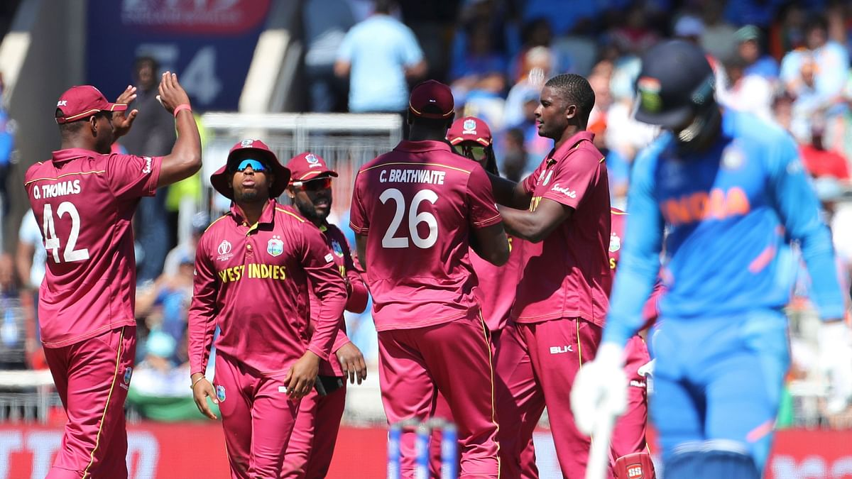 West Indies' captain Jason Holder, second right, celebrates with teammates the dismissal of India's K.L. Rahul.