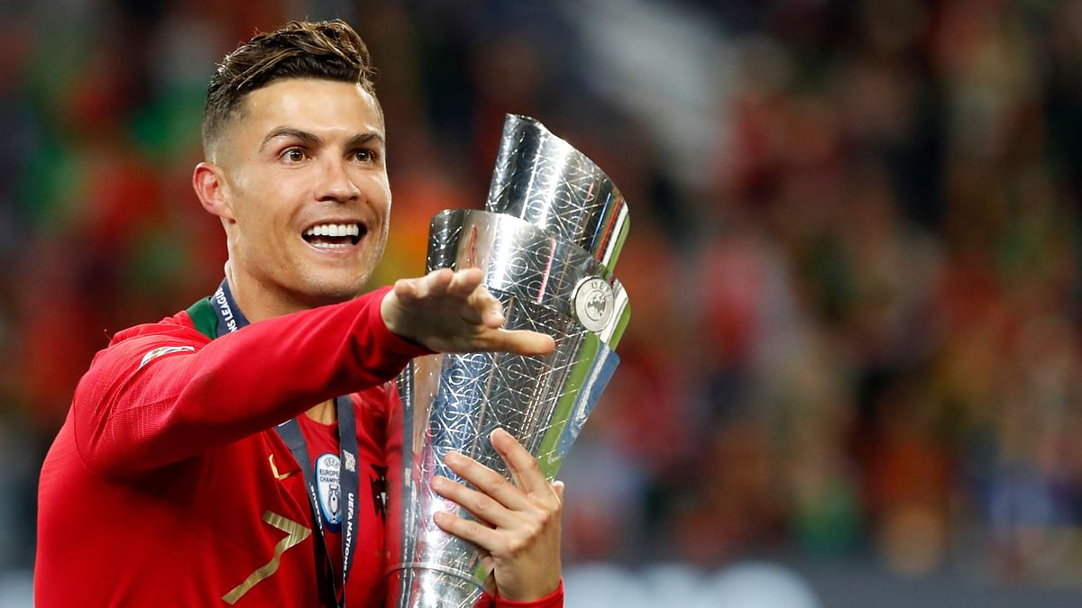 Portugal's Cristiano Ronaldo gestures as he holds the trophy after defeating the Netherlands 1-0 in the UEFA Nations League final soccer match.