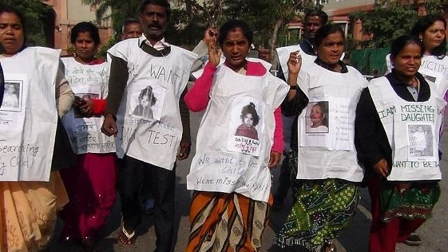 Nagarani (centre) protests along with other families who were affected by MSS in Delhi in 2013.