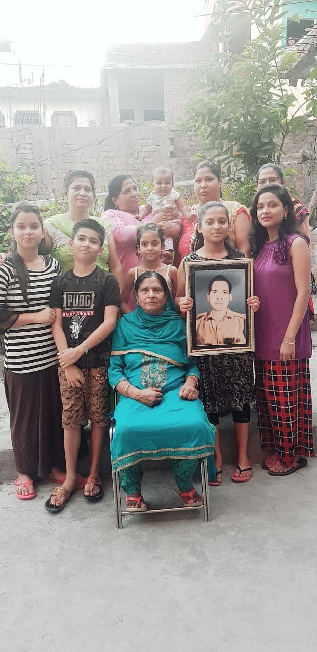 Rani Devi, her daughters and grandchildren with the picture of Sepoy Jagdish Lal.