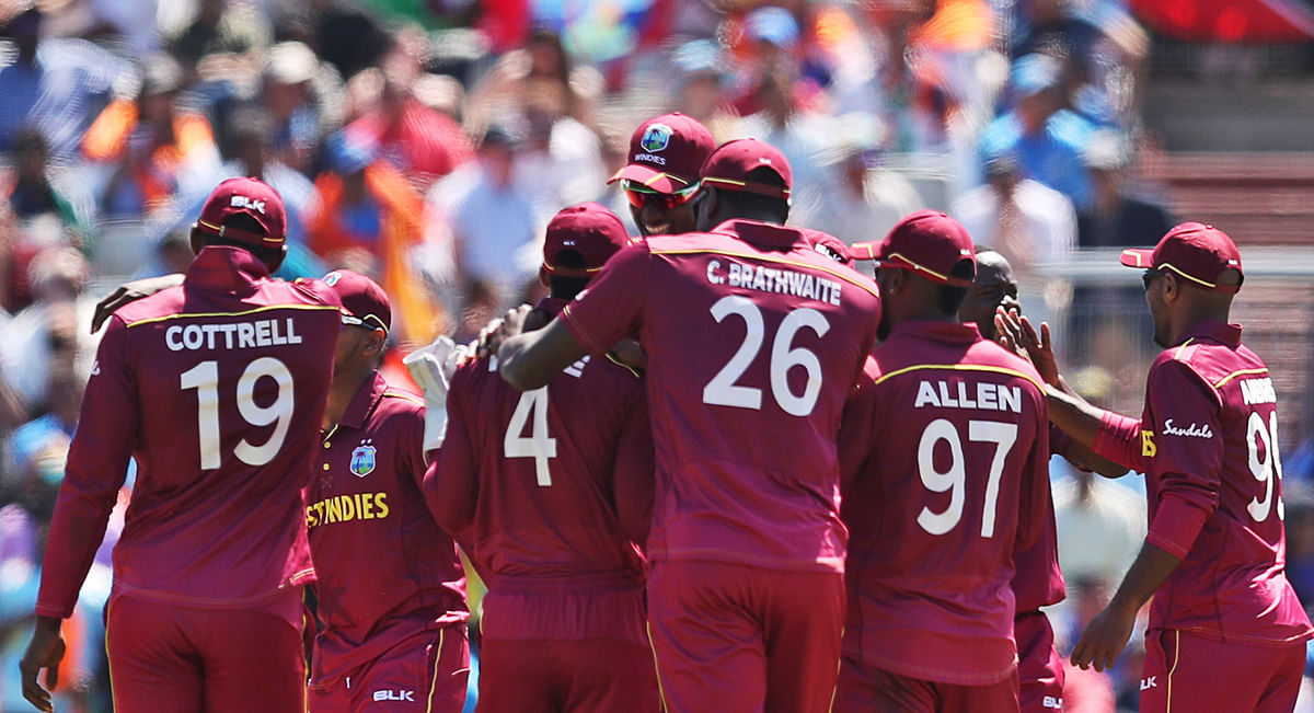 West Indies' cricketers celebrate the wicket of India's Kedar Jadhav during the Cricket World Cup match between India and West Indies at Old Trafford in Manchester.