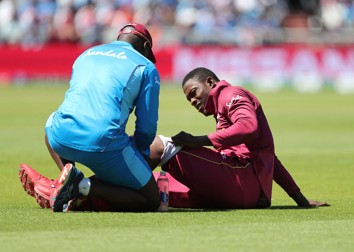 A member of team support staff attends to West Indies' Sheldon Cottrell during the Cricket World Cup match between India and West Indies.