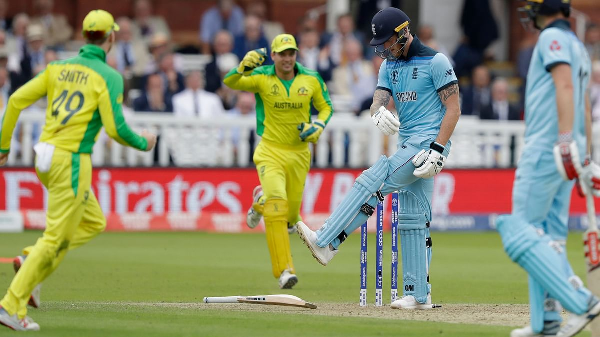 England's Ben Stokes kicks his bat after being clean bowled by Australia's Mitchell Starc, as Australia's Steve Smith looks on during the Cricket World Cup match between England and Australia at Lord's.