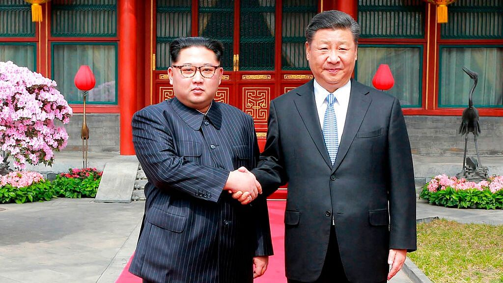 In this 27 March 2018 photo, North Korean Leader Kim Jong Un (L), shakes hands with Chinese counterpart Xi Jinping at Diaoyutai State Guesthouse in Beijing.