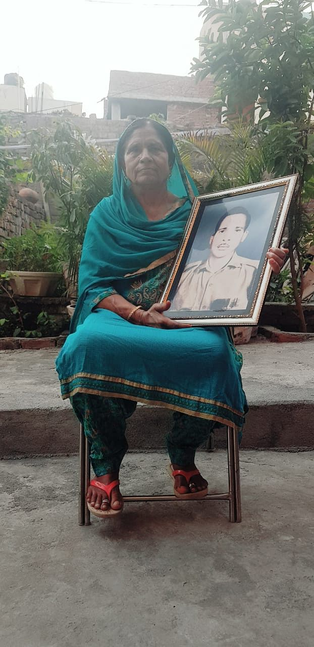 Rani Devi holding a picture of her missing husband, Sepoy Jagdish Lal.