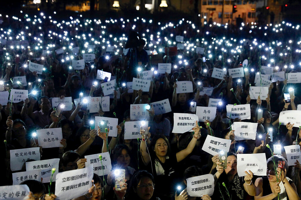 Hundreds of mothers holding placards and lit smartphones protest against the amendments to the extradition law in Hong Kong on 14 June 2019.