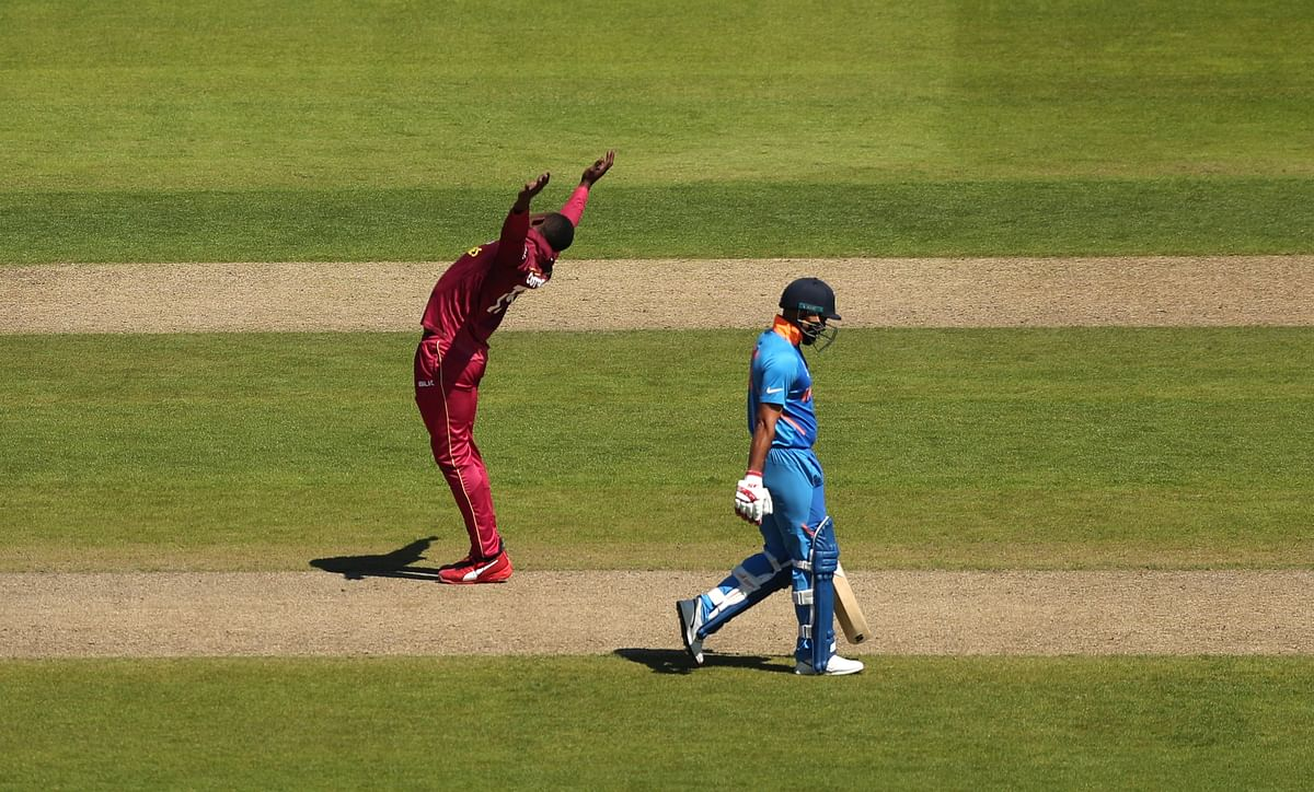 West Indies' Sheldon Cottrell celebrates after taking the wicket of India's Mohammed Shami.