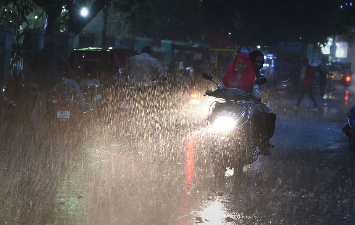 Commuters ride during sudden rain, providing respite after a prolonged dry and hot spell, in Chennai, on 26 June.