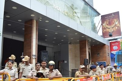 Bengaluru: Police personnel deployed outside the showroom of IMA Jewels on Lady Curzon Road where investors protest demanding their money back after a message about the death of the Group