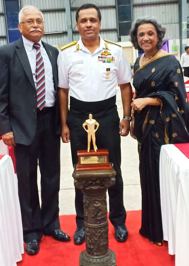 Philly (in uniform), flanked by his sister Sara Ipe and Brig Chacko Ipe, 64 Cavalry, stands behind the Simon George Pynumootil Trophy for 'Most Spirited Pilot'.