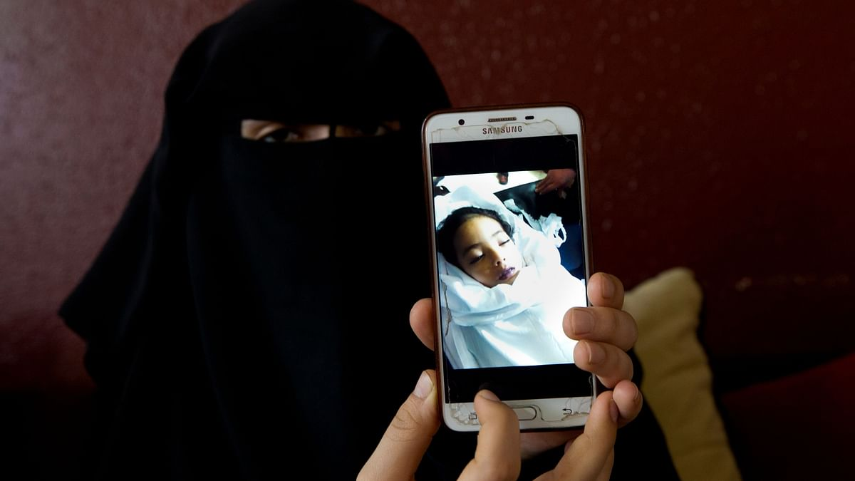 Muna Awad, mother of 5-year-old Aisha a-Lulu, shows a photo of her daughter while Aisha is in a Jerusalem hospital, at the family home in Burij refugee camp, central Gaza Strip.