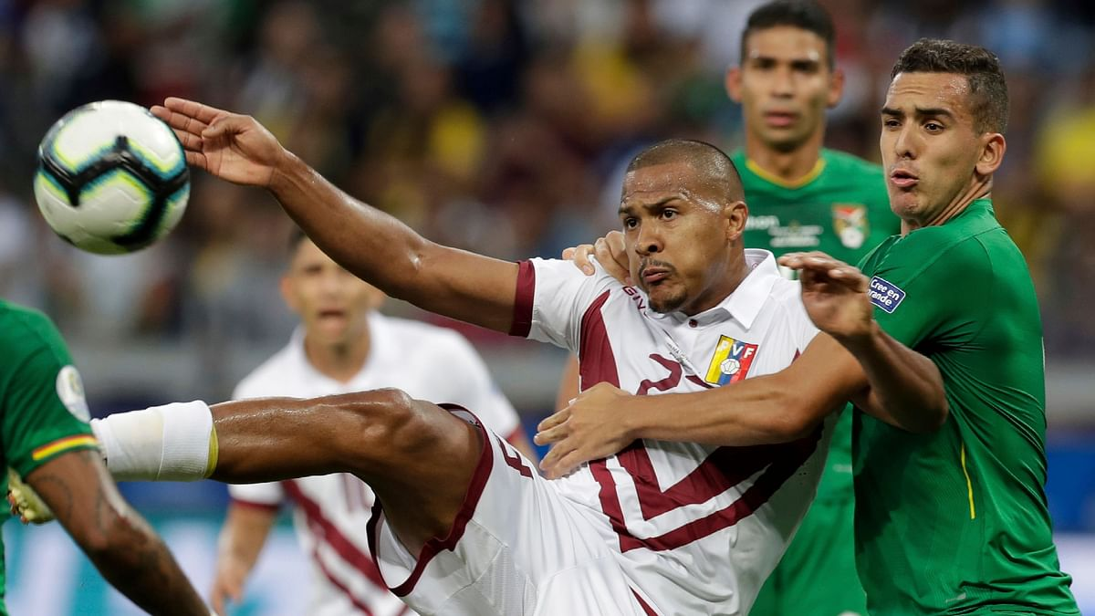 Venezuela's Salomon Rondon, left, fights for the ball with Bolivia's Marvin Bejarano during a Copa America Group A soccer match at Mineirao stadium in Belo Horizonte, Brazil.