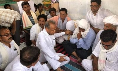 New Delhi: Rajasthan Chief Minister Ashok Gehlot consoles the family members of those who lost their lives after a massive tent erected for people attending a religious gathering in Rajasthan