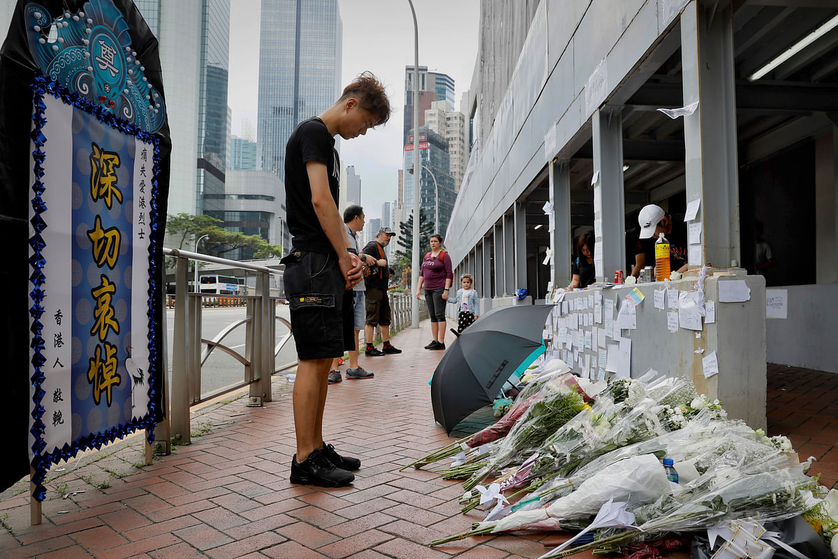 A man pays respect on the site where a man fell to his death a day earlier after hanging a protest banner against the extradition bill on the scaffolding of a shopping mall in Hong Kong, Sunday, June 16, 2019.