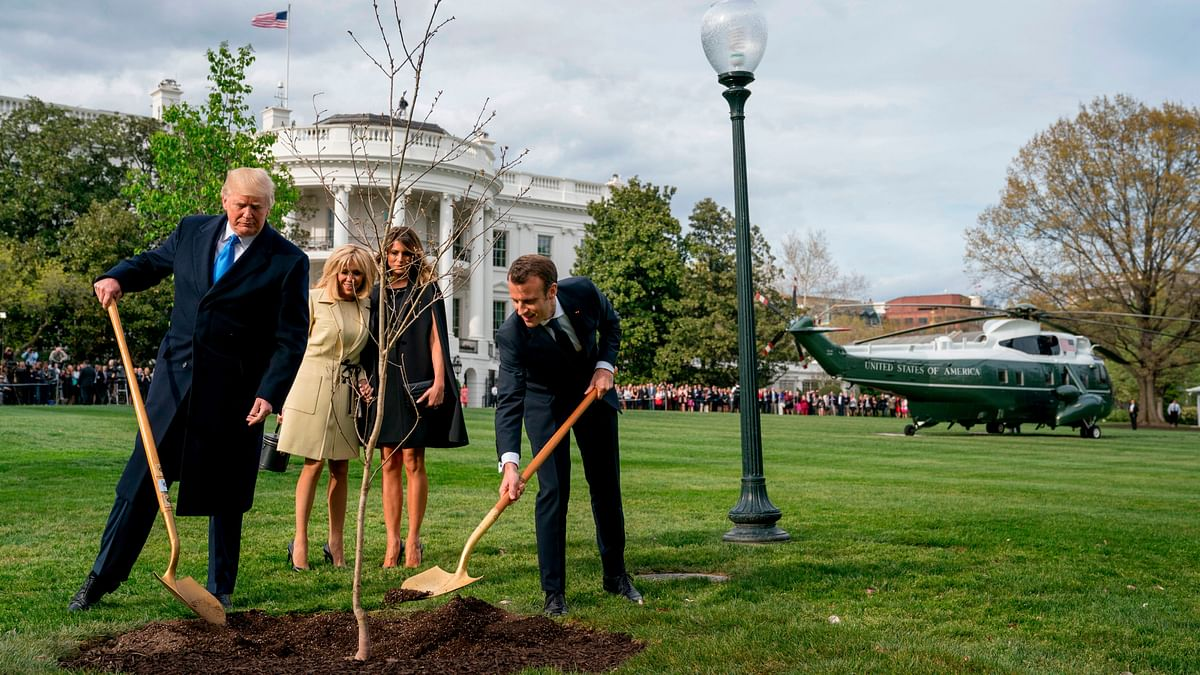 In this 23 April, 2018 file photo, Melania Trump, second right, and Brigitte Macron, second left, watch as President Donald Trump and French President Emmanuel Macron participate in a tree planting ceremony on the South Lawn of the White House in Washington.