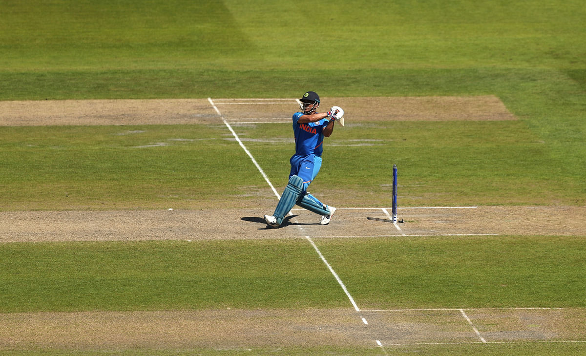 India's Mahendra Singh Dhoni scores a four as he bats during the last over of the Cricket World Cup match between India and West Indies.