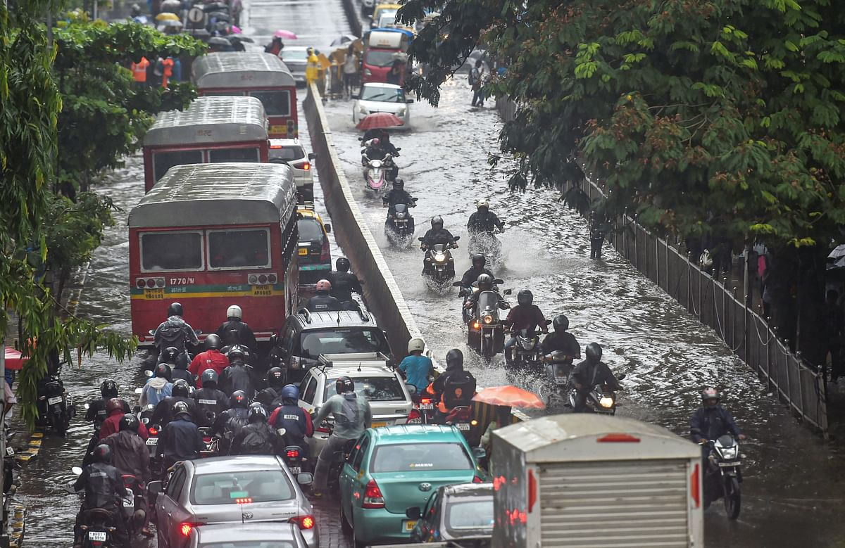 Vehicles move slowly through waterlogged streets during heavy monsoon rain in Mumbai.