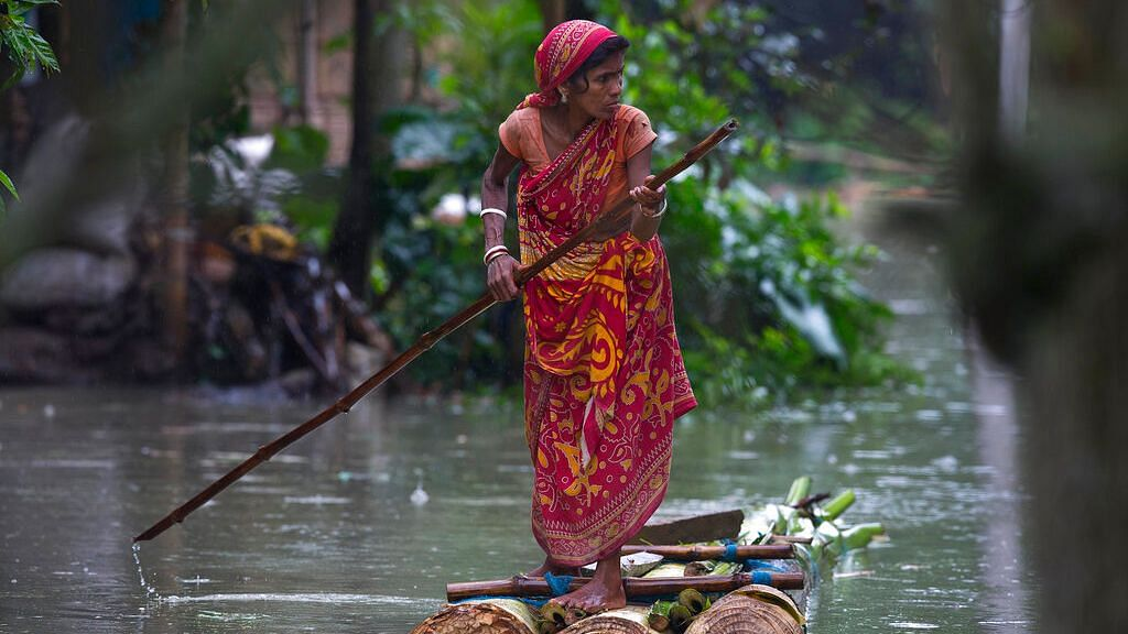 A woman rows a makeshift banana raft through flood waters in Burgaon in Assam, on Monday, 15 July 2019.