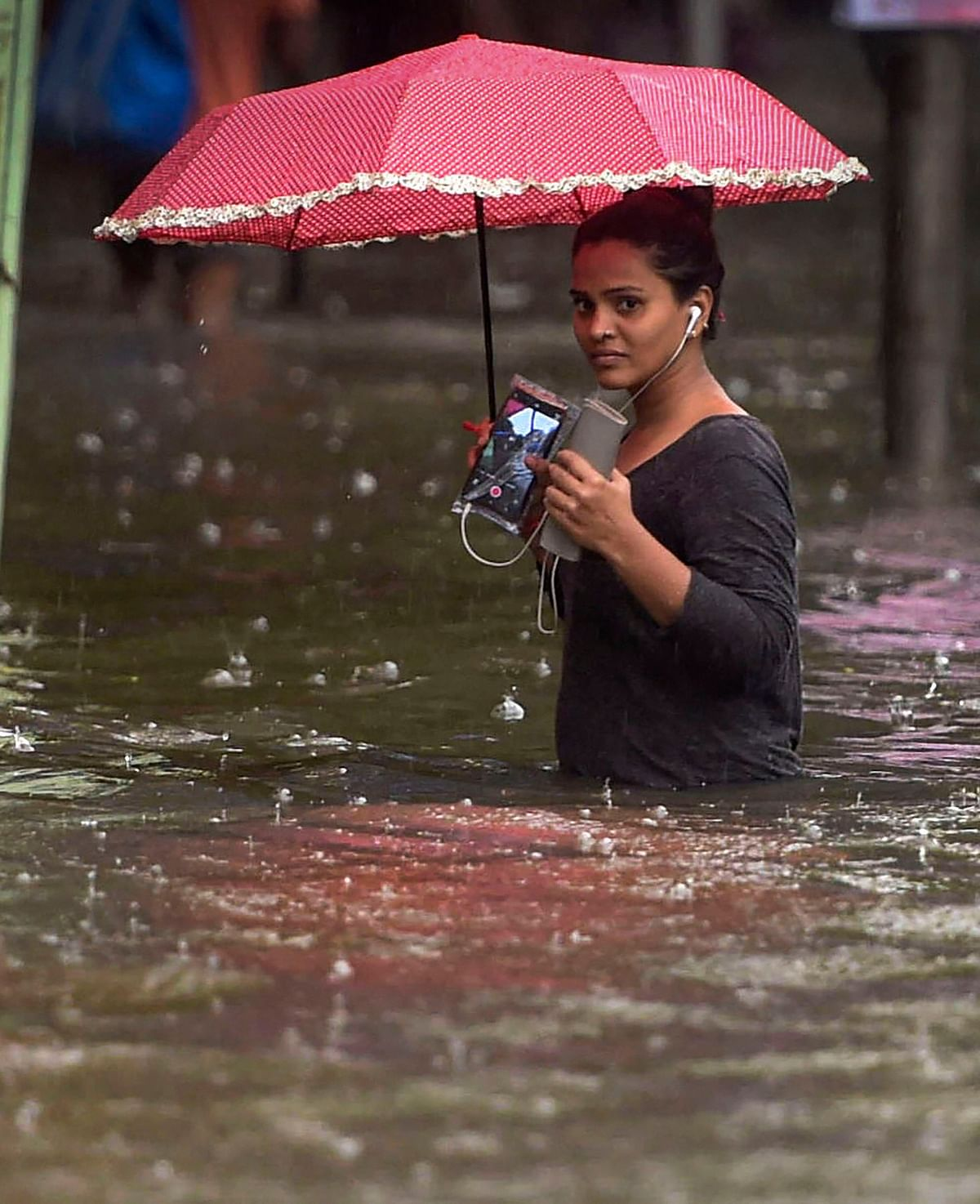 A woman wades through a waterlogged street during monsoon rain, in Mumbai.