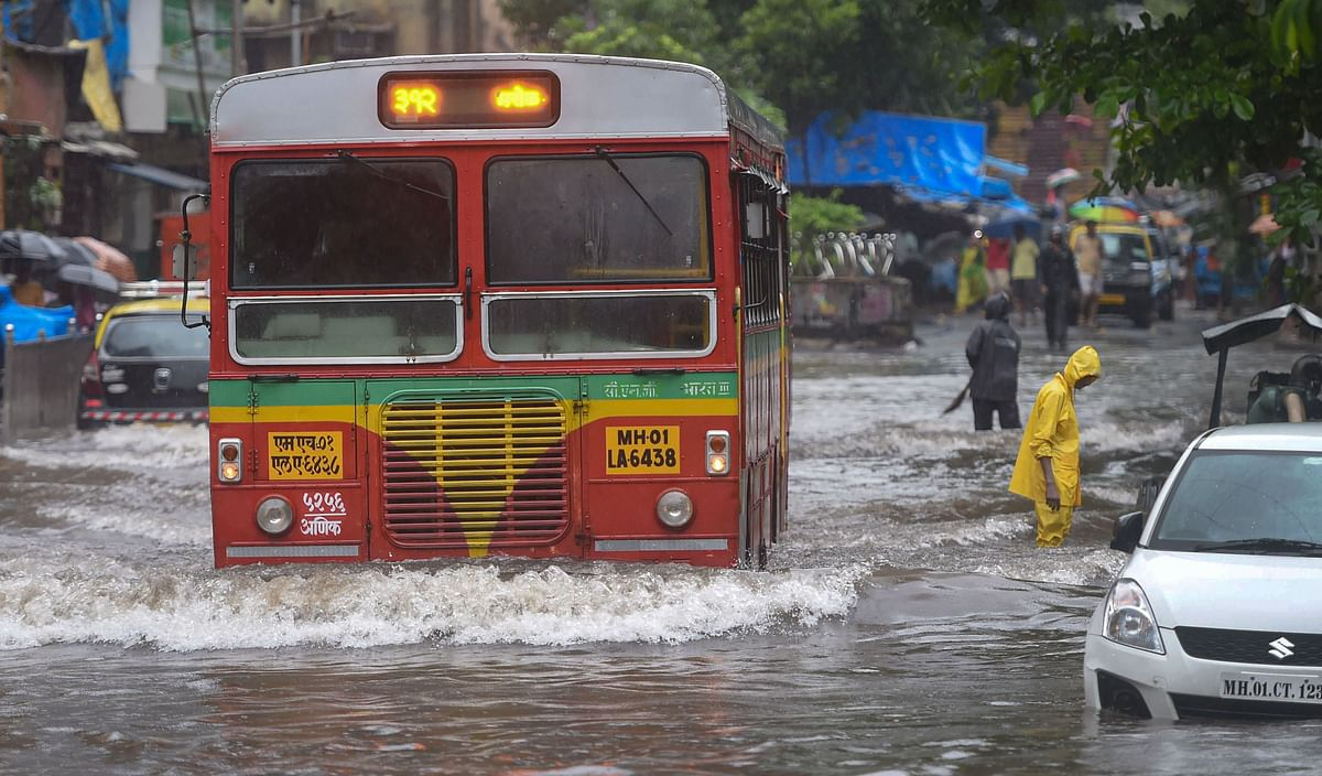 Vehicles move slowly through a waterlogged street following heavy monsoon rain, in Mumbai.
