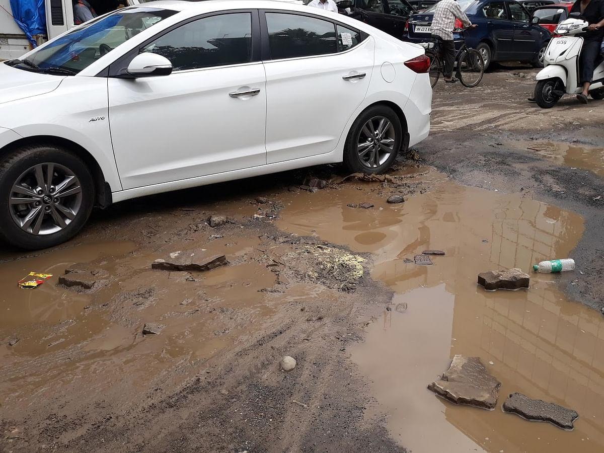 A pothole and a muddy road at Jogeshwari East.