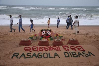 Puri: Sand artist Sudarshan Patanaik creates a sand art on Rasagola, a desert at Puri sea beach in Odisha on July 16, 2016. Odisha and West Bengal are fighting for the GI tag and paten over Rasagola. (Photo: IANS)