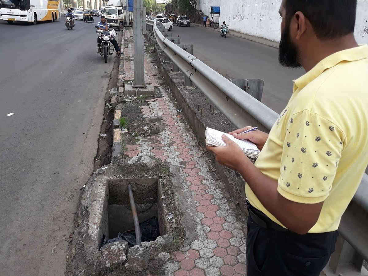 Mr Irfan Machhiwala takes note of an open manhole near the highway.