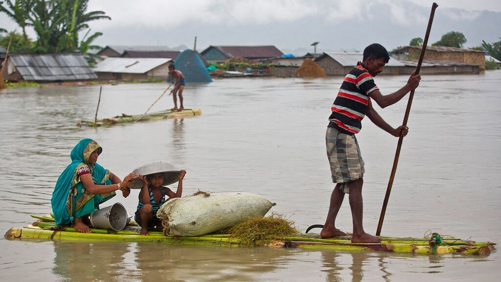 Flood affected villagers move on a makeshift bamboo raft in Katahguri village along the river Brahmaputra, east of Gauhati on Sunday.