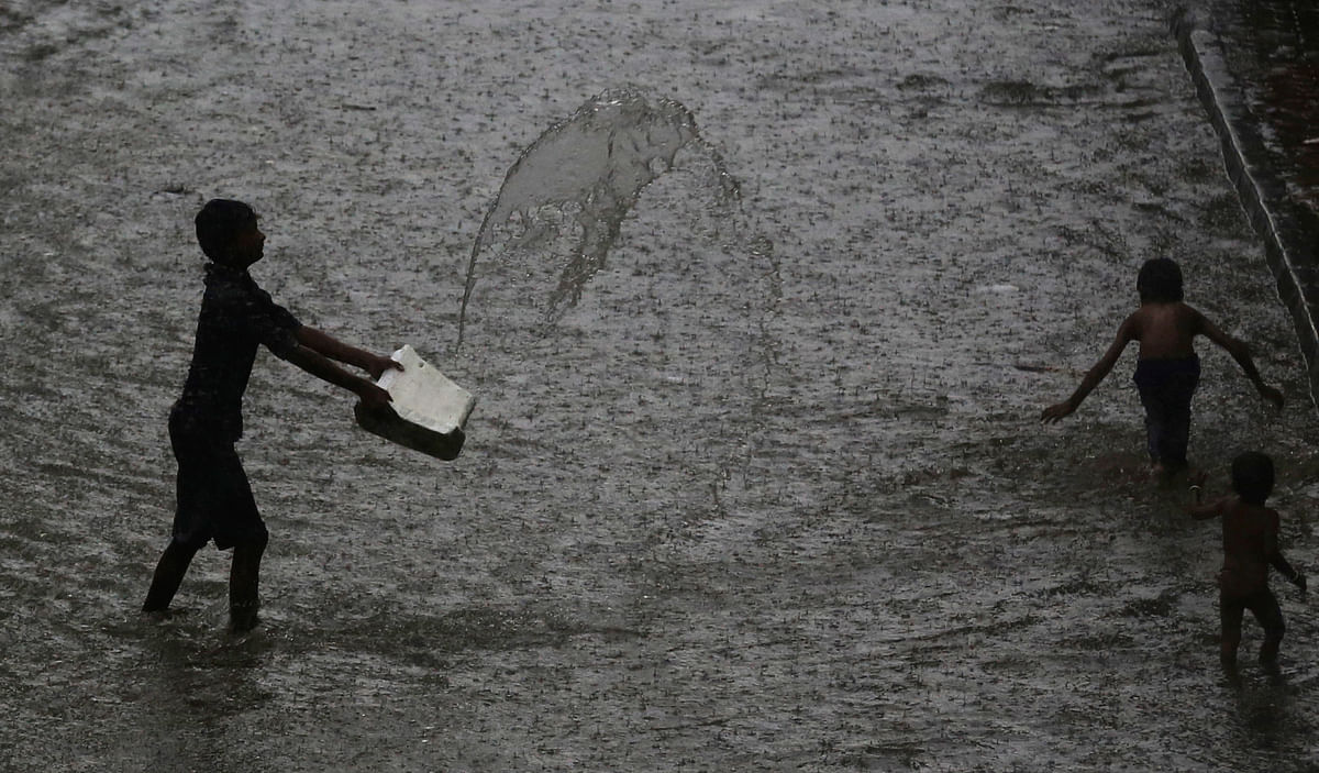 Children play at a waterlogged street during monsoon rains in Mumbai.