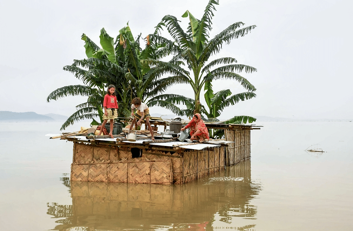 A family marooned on the top of a hut in the flood-hit locality of Panikhaiti in Kamrup district of Assam, on Monday, 15 July 2019.