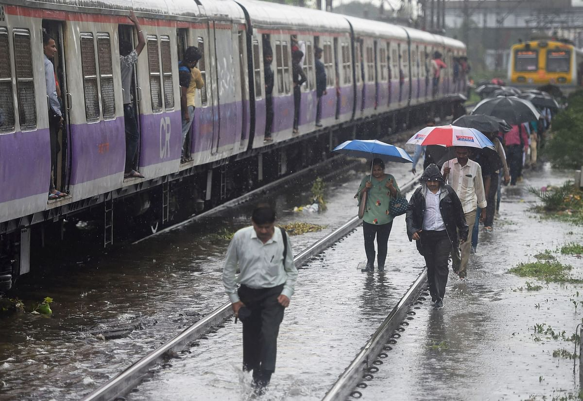 People walk on the railway tracks as heavy monsoon rains hit the local train services, in Mumbai.