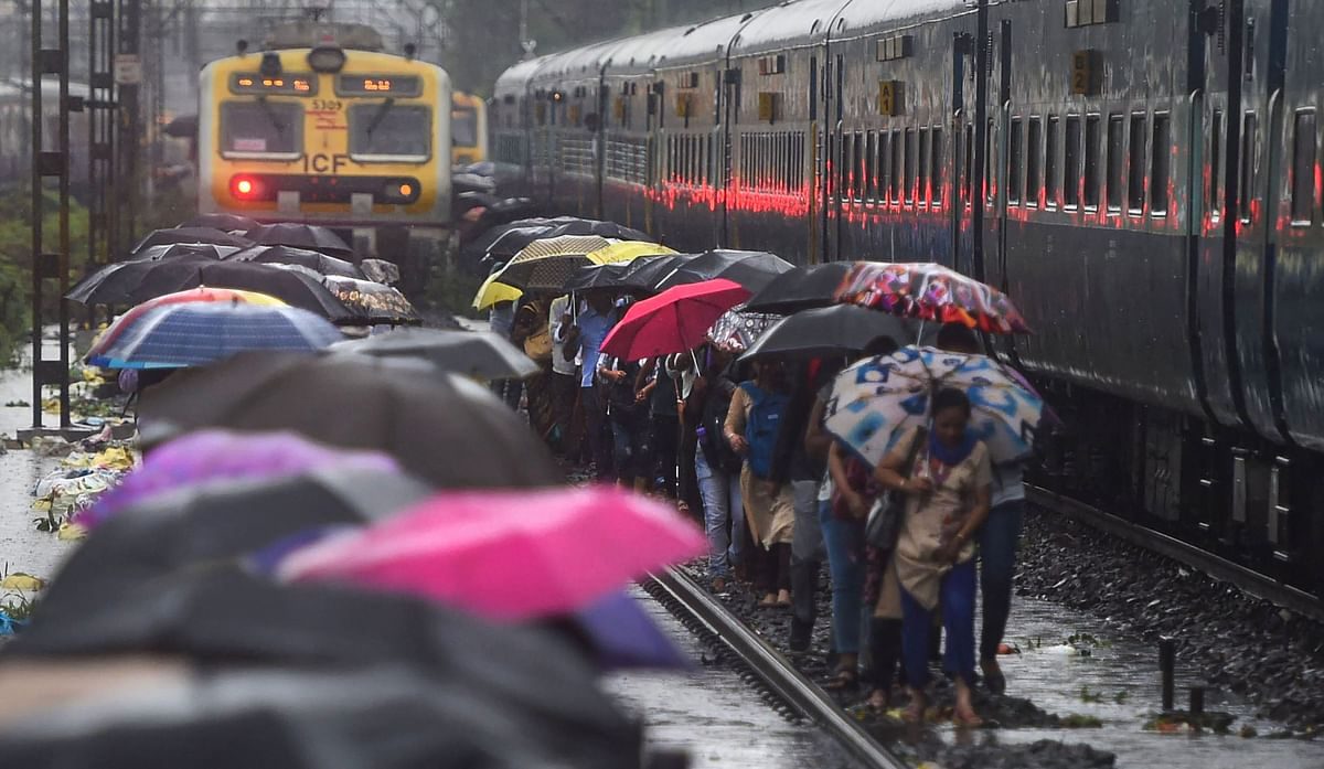 People walk on the railway tracks as heavy monsoon rains hit the local train services.