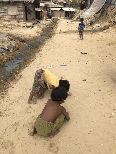 Rohingya kids engrossed in their game, beside an open drain that overflows and floods during the monsoon.