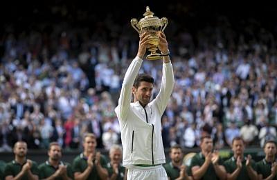 LONDON, July 15, 2019 (Xinhua) -- Novak Djokovic of Serbia holds the trophy after winning the men