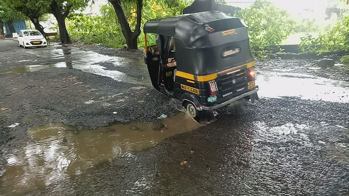 An auto tries to drive through a pothole at Royal Palm road, in Aarey Colony, Goregaon East.