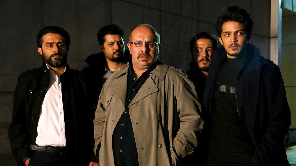 This undated promotional handout still from the Iranian state TV series, 'Gando', shows actor Payam Dehkordi, center, who plays a character apparently based on Washington Post journalist Jason Rezaian, among other actors.