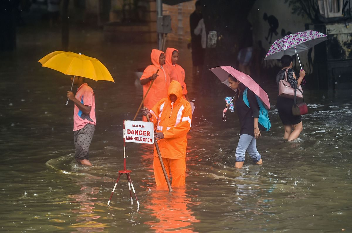A Municipal worker stands guard to warn pedestrians of an open manhole on a waterlogged street following heavy monsoon rains.
