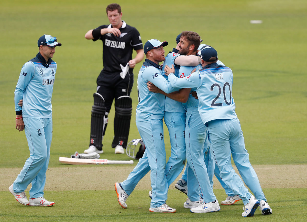 England's Liam Plunkett, centre, celebrates with teammates after taking the wicket of New Zealand's captain Kane Williamson caught behind during the World Cup final.