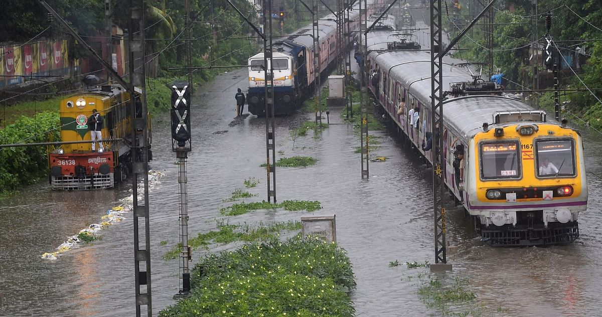 Suburban trains chug on water-logged tracks during heavy rains, in Mumbai.