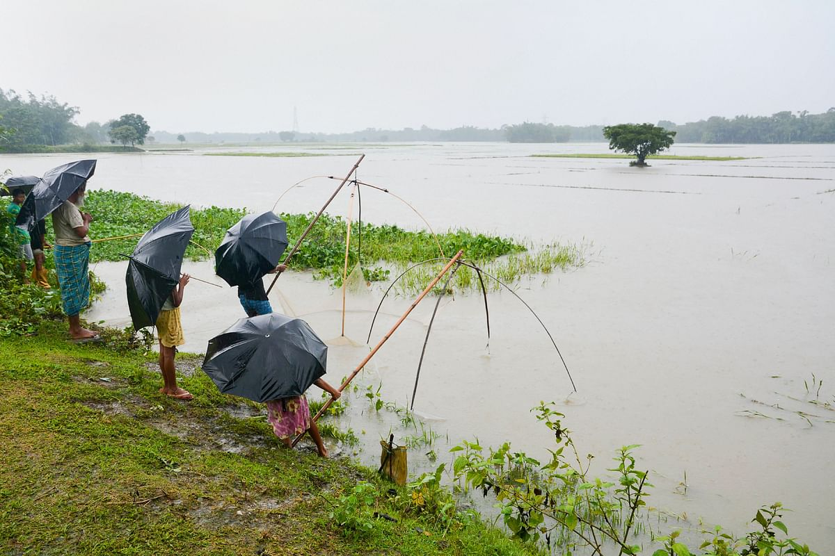 Villagers spread their fishing net to catch fish in flood waters at Hakata, in Baska, Saturday, 13 July.